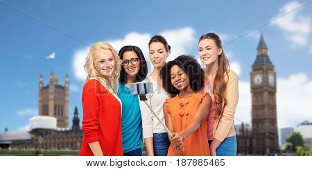 travel, tourism and people concept - international group of happy smiling different women taking picture with smartphone on selfie stick over london big ben tower background