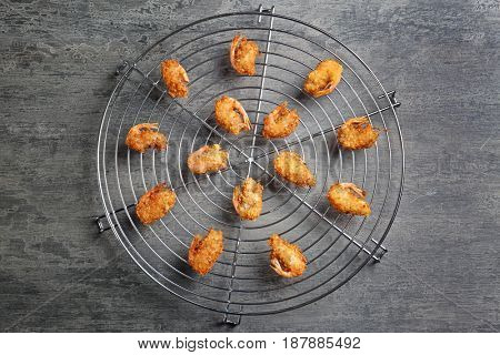 Cooling rack with delicious coconut shrimps on gray background