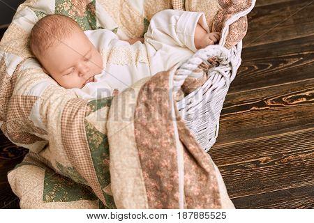 Sleeping caucasian child. Basket with baby, wood background. Good night sleep tight.