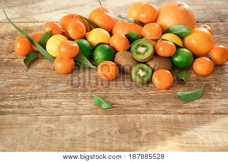 Different fresh citrus fruits with halves of kiwi on wooden background
