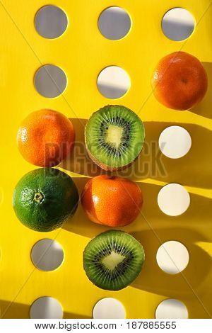 Fresh tangerines, lime and halves of kiwi on holey background