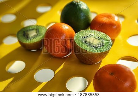 Fresh tangerines, lime and halves of kiwi on holey table