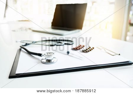 View of stethoscope drug and equipment on foreground table with computer laptop Health care and Medical concept.
