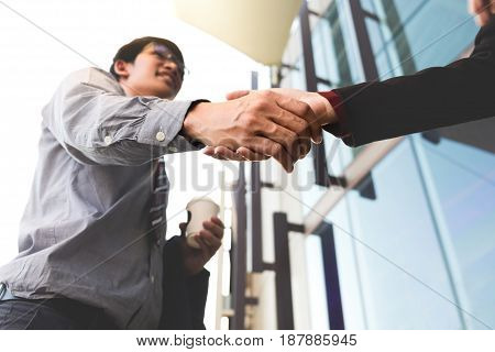 Happy smiling business man shaking hands after a deal finishing up a meeting business outdoors concept.