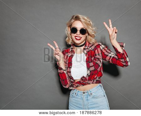 Beautiful model in stylish outfit and sunglasses showing two fingers and smiling at camera.