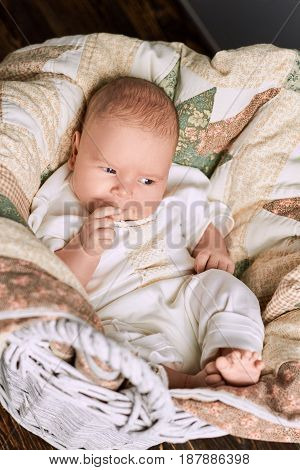 Thoughtful caucasian infant. Basket with blanket and child. Baby brain development.