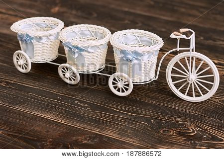 White tricycle flower basket. Baskets with bows, wooden surface. Buy vintage souvenirs.