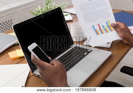 African-american businessman working with mobile and laptop in modern office, crop, over shoulder, empty screen for copy space