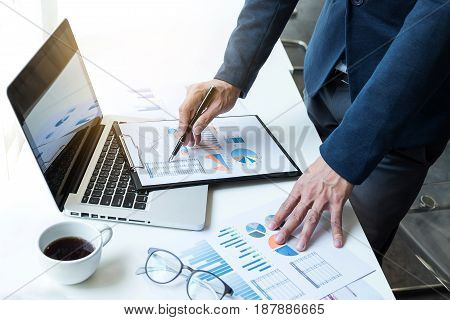Business man working at office with laptop and documents on his desk. Analyze plans papers hands keyboard .