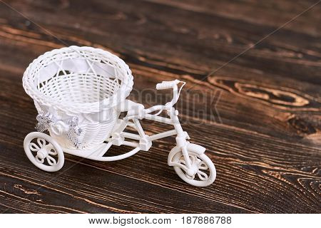 Plastic tricycle flower basket. White toy on brown wood.