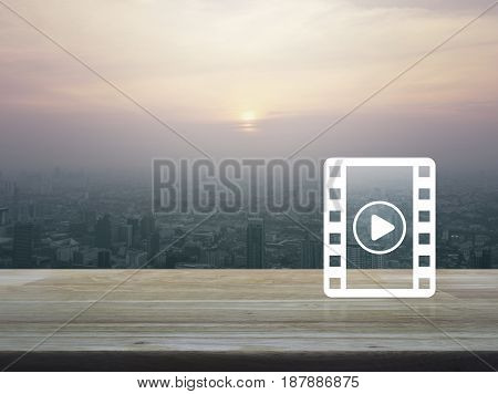 Play button with movie icon on wooden table over aerial view of cityscape at sunset vintage style Cinema online concept