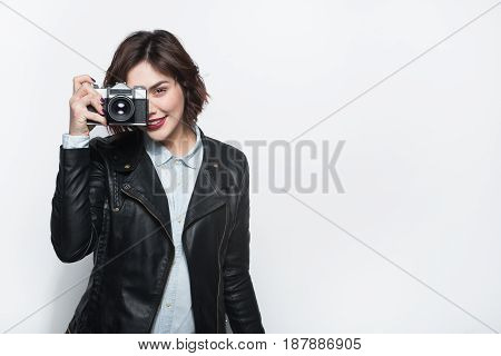 Pretty brunette in leather jacket using retro photo camera on white background looking at camera.