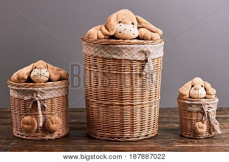 Laundry baskets with soft toys. Baskets on wooden surface. Cute household items.