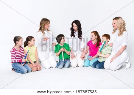 Health care education. Happy children with toothbrushes and female doctors on white isolated studio background, copy space