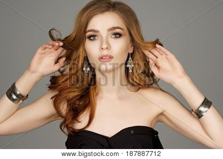 Beautiful model with long wavy red hair and jewelry. Perfect makeup. Girl wearing earrings and bracelets.