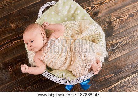 Baby in basket, top view. Caucasian kid wrapped in blanket.