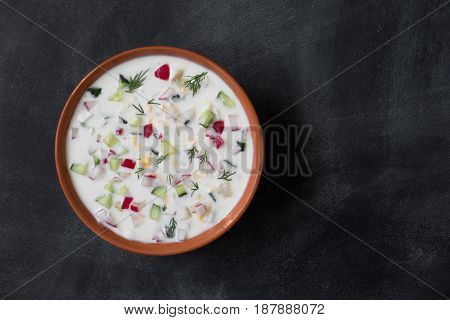 Summer yoghurt russian cold soup with radish, cucumber, and dill on table, top view.Okroshka.