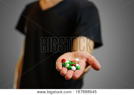 A Man In A Black T-shirt Holding A Colorful Pill. Bright Colored Candy. Isolated