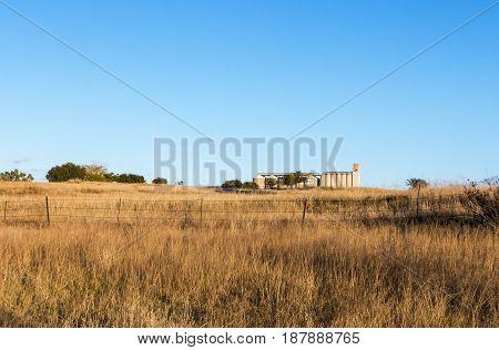 Autumn Grass Against Rural Agrucultural Grain Silos Landscape