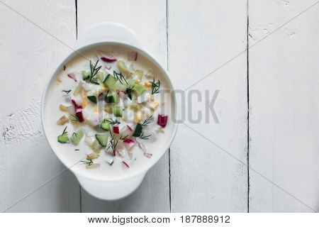 Summer yoghurt russian cold soup with radish, cucumber, and dill on table, top view.Okroshka. Copy space for text