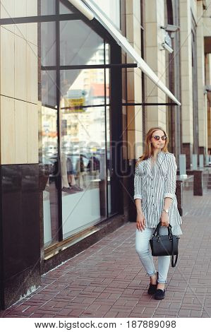 Young woman walking around the city wearing light clothes