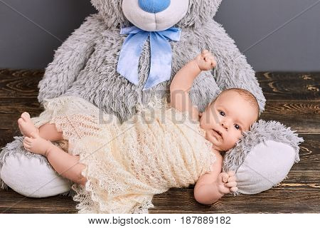 Cute child and teddy bear. Infant boy wrapped in shawl. Effective methods of upbringing.