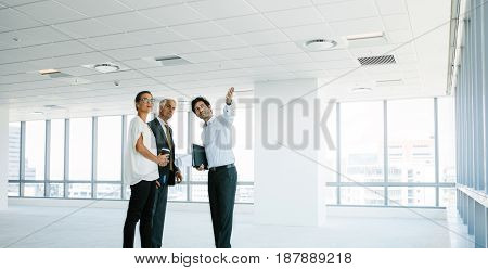 Male real estate agent showing new office space to clients. Business people discussing and looking at new office with estate broker.