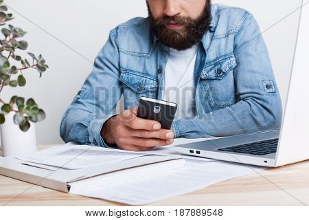 A Film Effect. Portrait Of Bearded Man In Jean Shirt Hoding Smartphone In His Hand While Working Wit