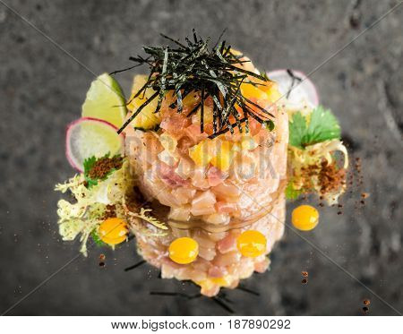 Fresh sea-bass tartar with garnish over concrete background
