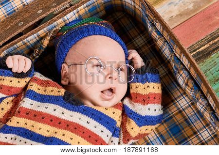 Caucasian baby in spectacles. Infant with opened mouth. The young genius.