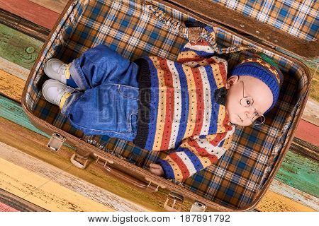 Child lying in opened suitcase. Little kid in spectacles. Tips for beginner traveler.