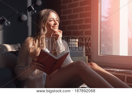 Thoughtful woman with the book looking at the window and smiling. Horizontal indoors shot.