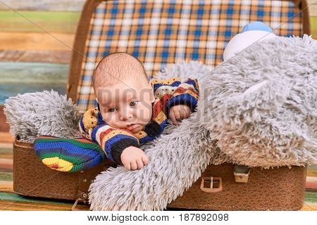Infant with a teddy bear. Child in opened suitcase. The travel buddies.