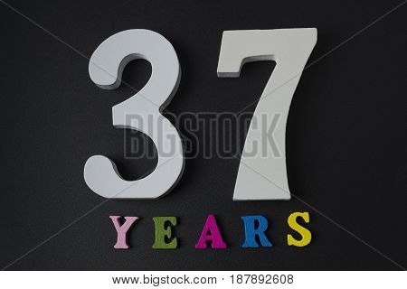 Letters And Numbers Thirty-seven Years On A Black Background.