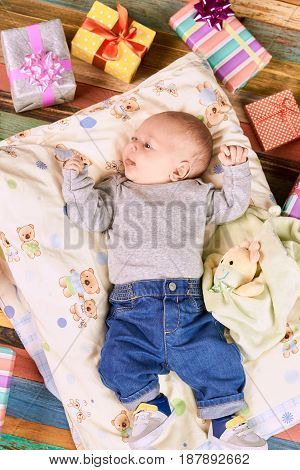 Baby and presents. Child on a pillow. Celebrate the first Christmas.