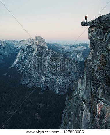 A Fearless Hiker Is Standing On An Overhanging Rock Enjoying The View Towards Famous Half Dome At Gl