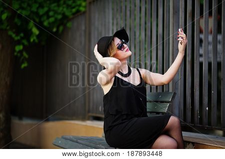 Blonde Woman On Black Dress, Sunglasses, Necklaces And Hat Sitting On Bench With Mobile Phone At Han