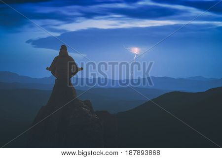 Silhouette of human meditating in sitting yoga position on the top above the mountain valley. Zen meditation peace. Instagram stylization.