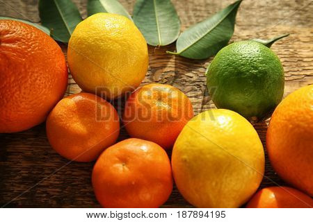 Appetizing fresh citrus fruits with green leaves on wooden background