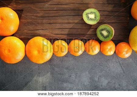 Citrus fruits and wooden board with halves of sliced kiwi on grunge background