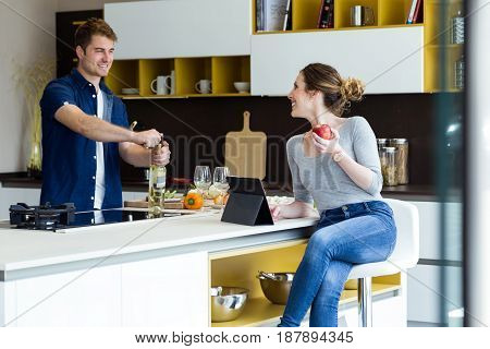 Handsome Young Man Opening Wine Bottle While His Wife Using Digital Tablet In The Kitchen.