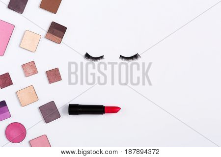Makeup cosmetics and essentials frame on white background. Top view, flat lay with copy space. Beauty tools palettes collection, lipstick, eyeshadow, blush, foundation and more