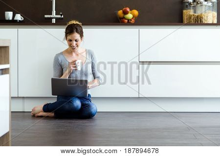 Portrait of beautiful young woman using her digital tablet in the kitchen at home.