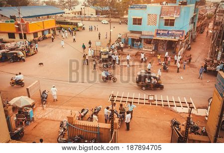 KARNATAKA, INDIA - FEB 10, 2017: Road in small indian city with bikes taxi and walking people outside on February 10, 2017. Population of Karnataka state is 62000000 people