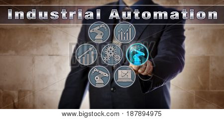 Blue chip manufacturing manager activating a robotic arm icon on a virtual Industrial Automation control panel. Industry concept for the automation of manufacturing and material handling processes.