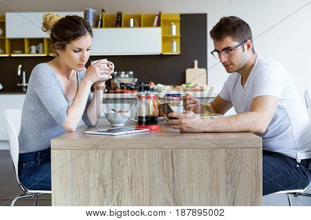 Portrait of beautiful young couple using digital tablet and smartphone while enjoying the breakfast.