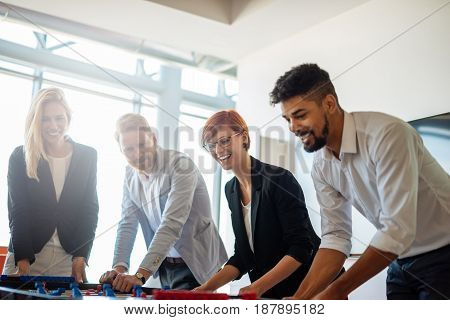 Photo of businesspeople having fun on a break playing table football.