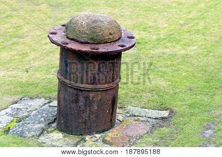 Old steel and concrete boat mooring bollard on stone base