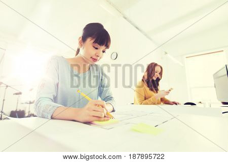 business, startup and people concept - creative or architect woman with blueprint writing on sticker at office