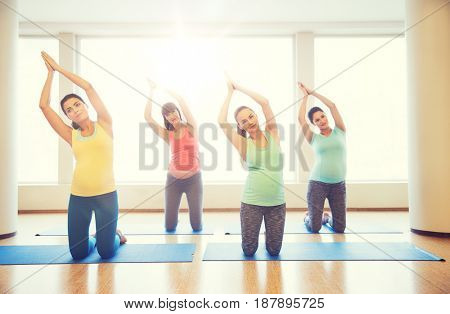 pregnancy, sport, fitness, people and healthy lifestyle concept - group of happy pregnant women exercising on mats in gym